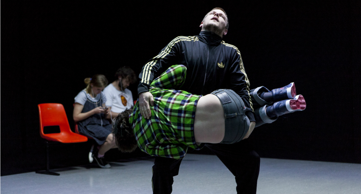 One performer holds another, his body balanced against his knees and looks up at the ceiling.