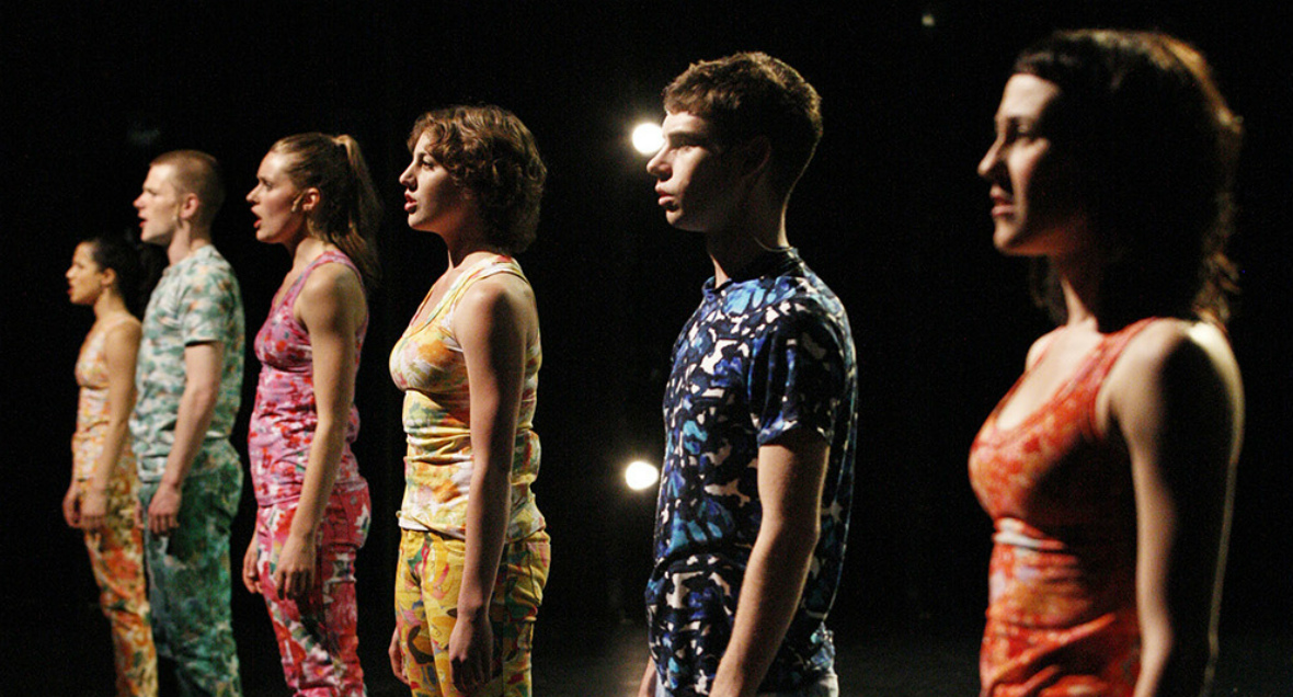 Dancers stand in a line wearing colourful clothing, staring outward.