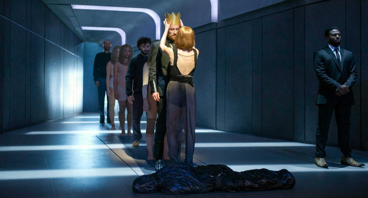 Performers stand in a line down the centre of the stage while a woman places a crown on a man's head. A man in an suit stands off to the side.