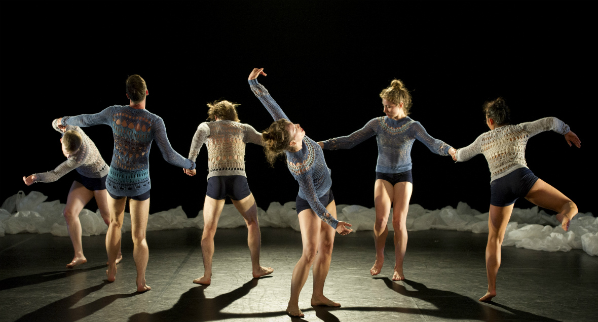 Dancers hold hands with arms and legs outstretched.