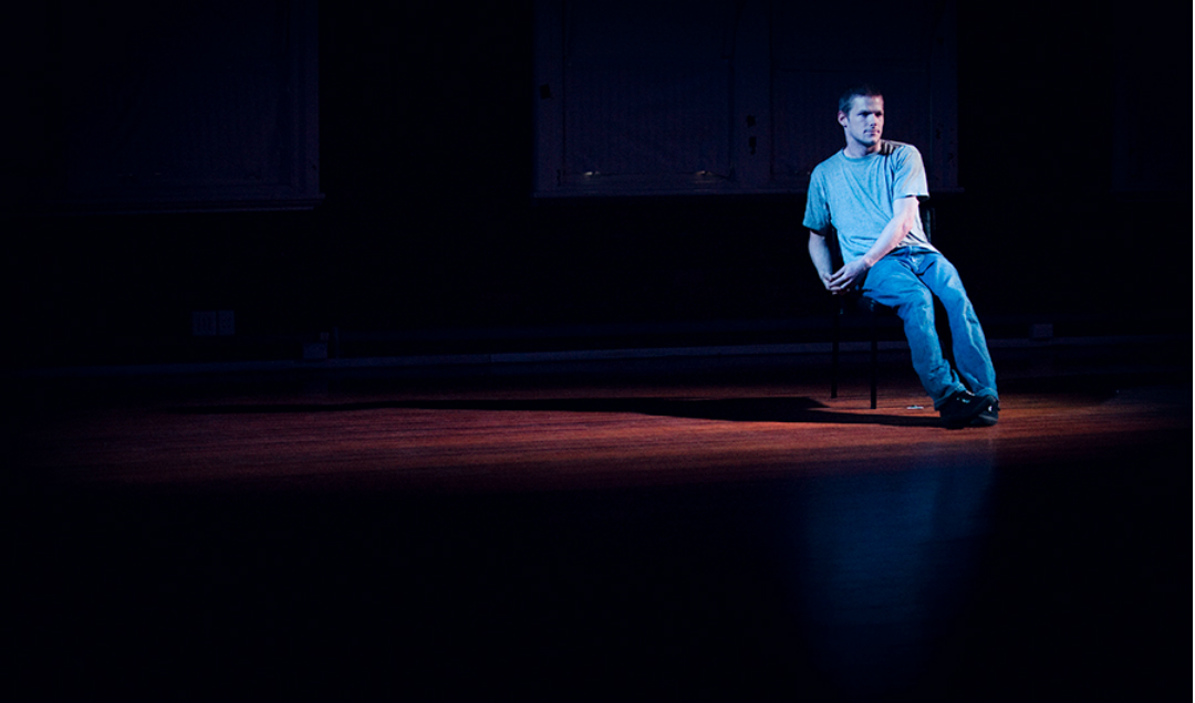 A young man, Alisdair Macindoe, sits on a chair in a small pool of light on a wooden floor dressed in light denim clothes.