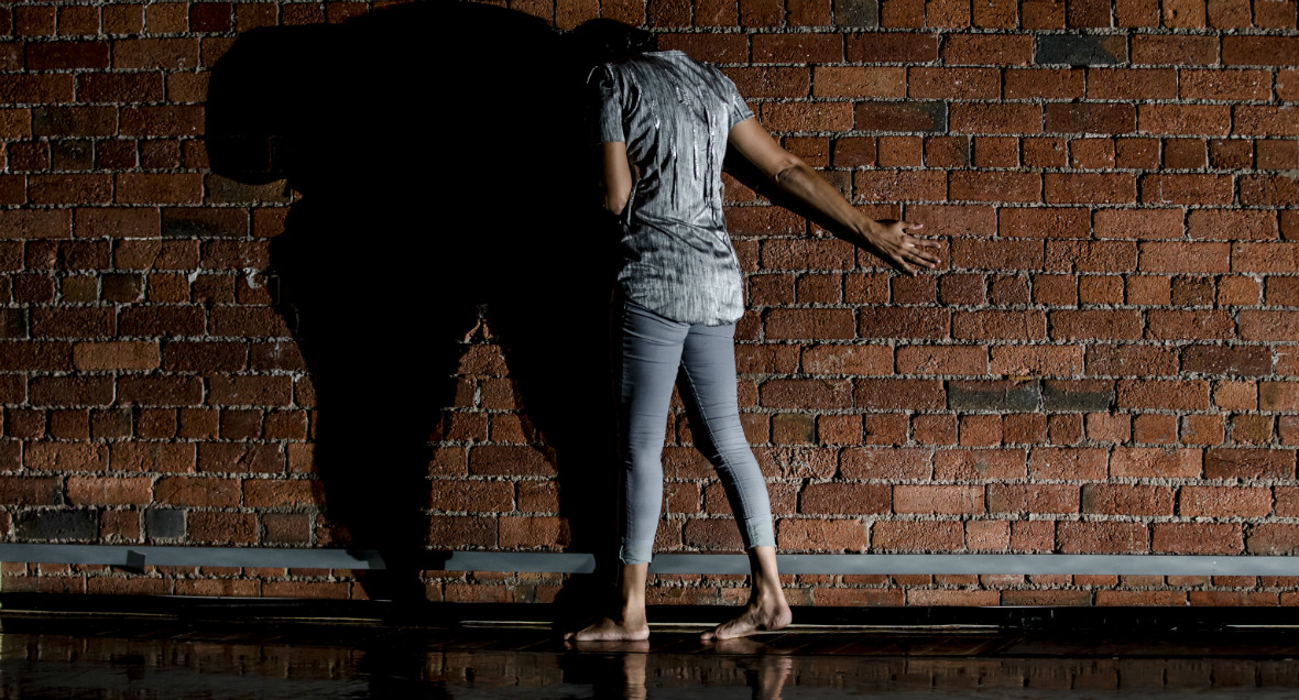A dancer faces a brick wall with their feet apart and arm stretched out behind them.