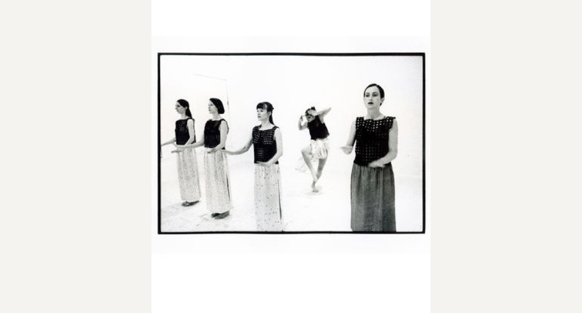 A greyscale image of four dancers in a line with hands held horizontally out at mid-level in unison while another dancer makes an angular movement behind them.