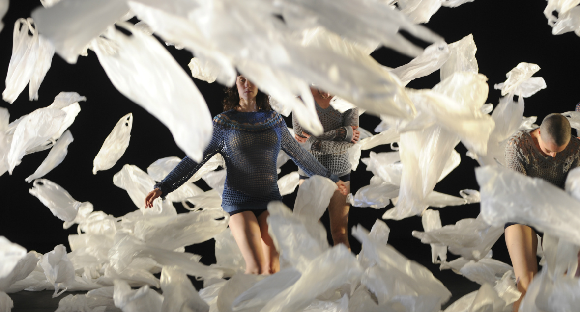 Dancers stand amongst a sea of plastic bags falling around them.