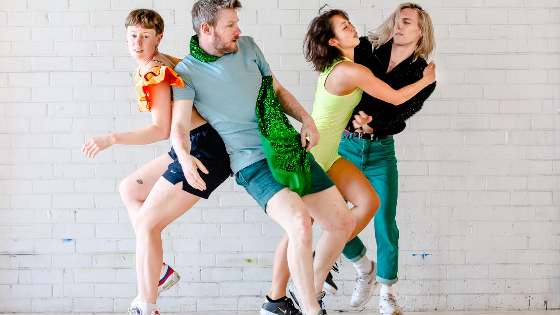 4 dancers in brightly coloured clothing lean on and move in close proximity to each other in front of a white brick wall