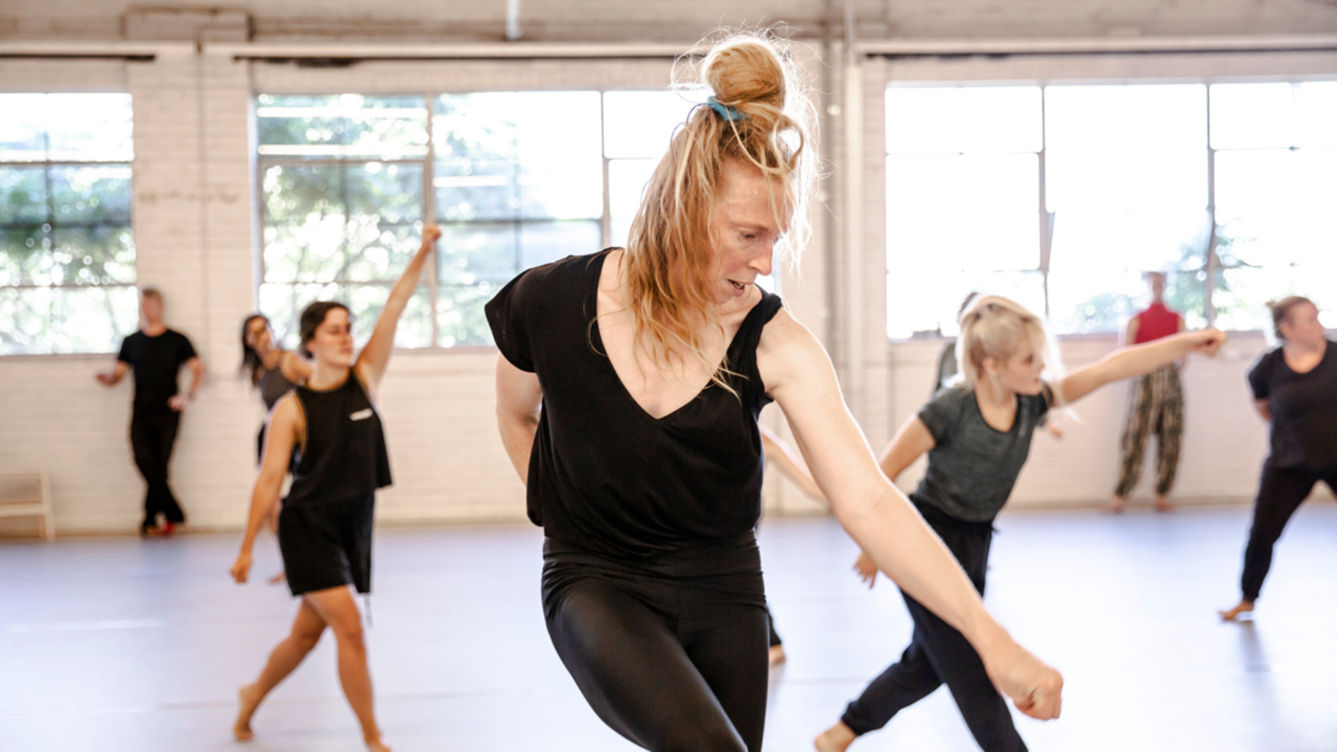 A close up of a dancer striking a strong pose with one arm extended down. Dancers in the background also strike strong poses with arms extended in various directions