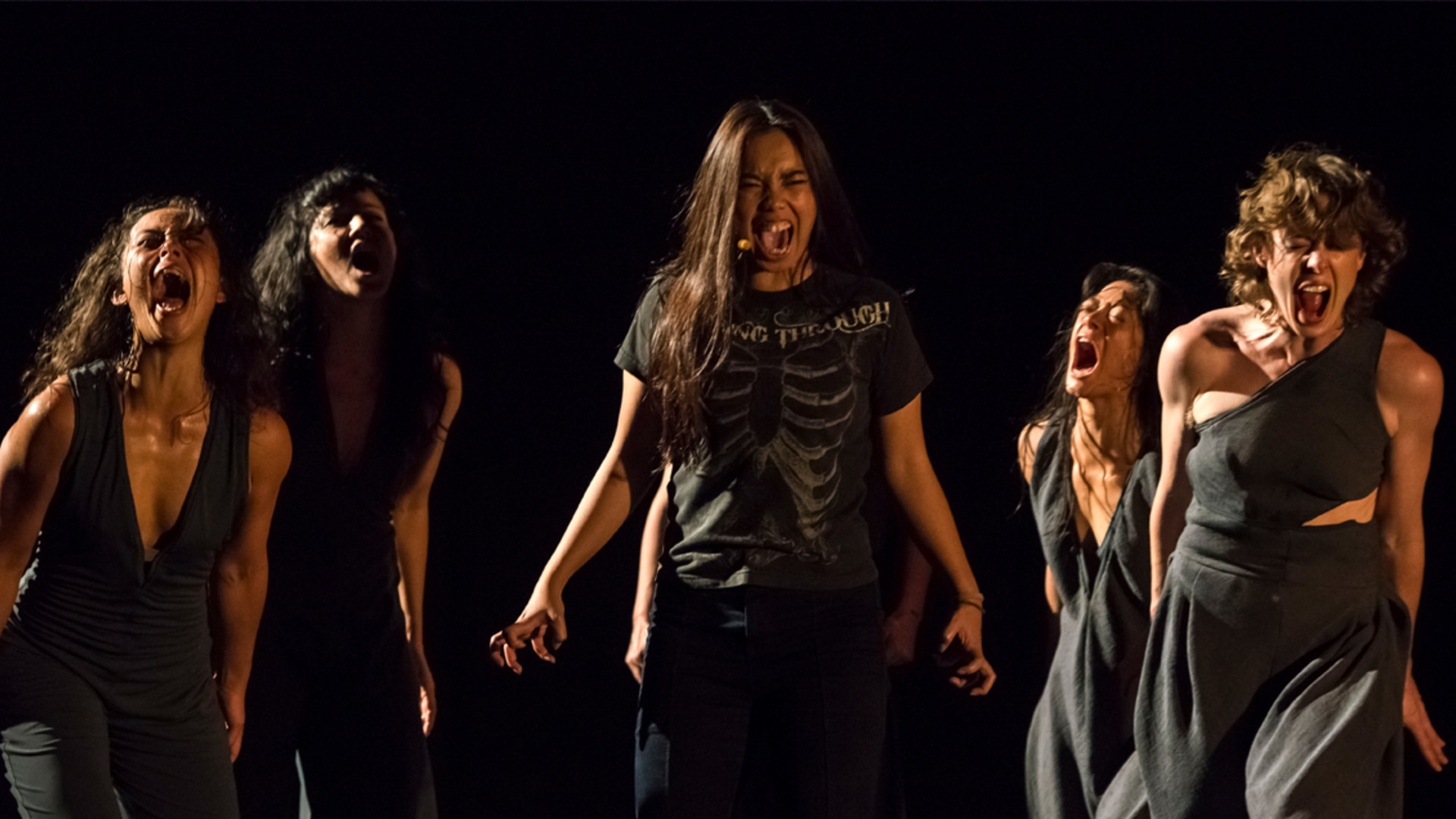 A singer in the centre, surrounded by four dancers, all screaming with their fists clenched.