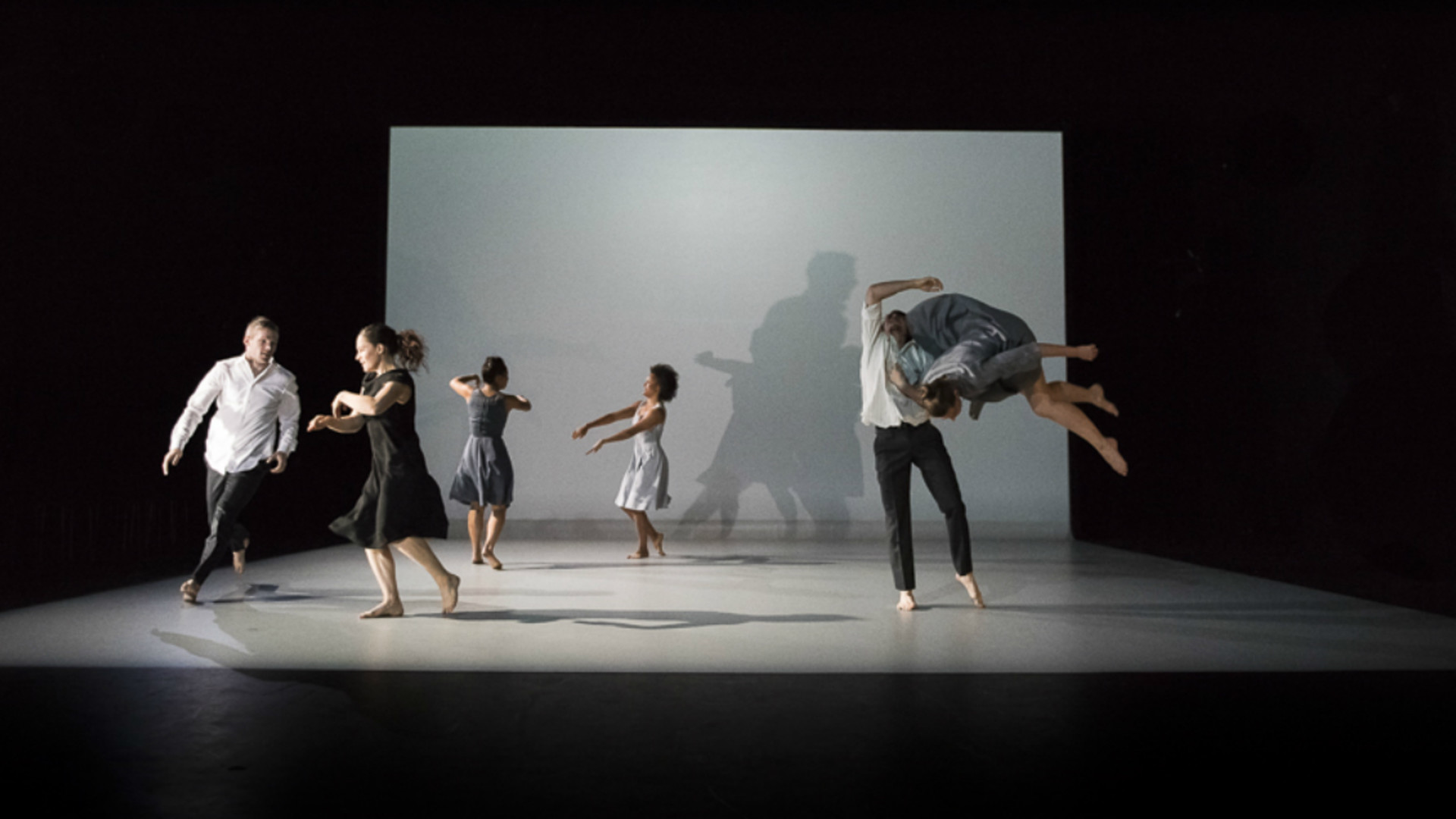 Dancers are scatterd around the stage with one lifting another in the air.