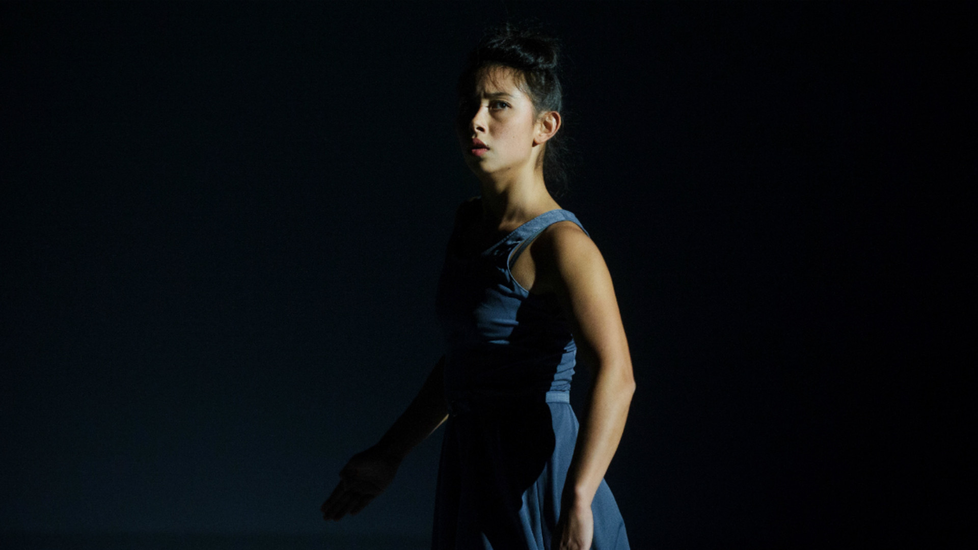 A dancer stands with her arms by her side looking out.
