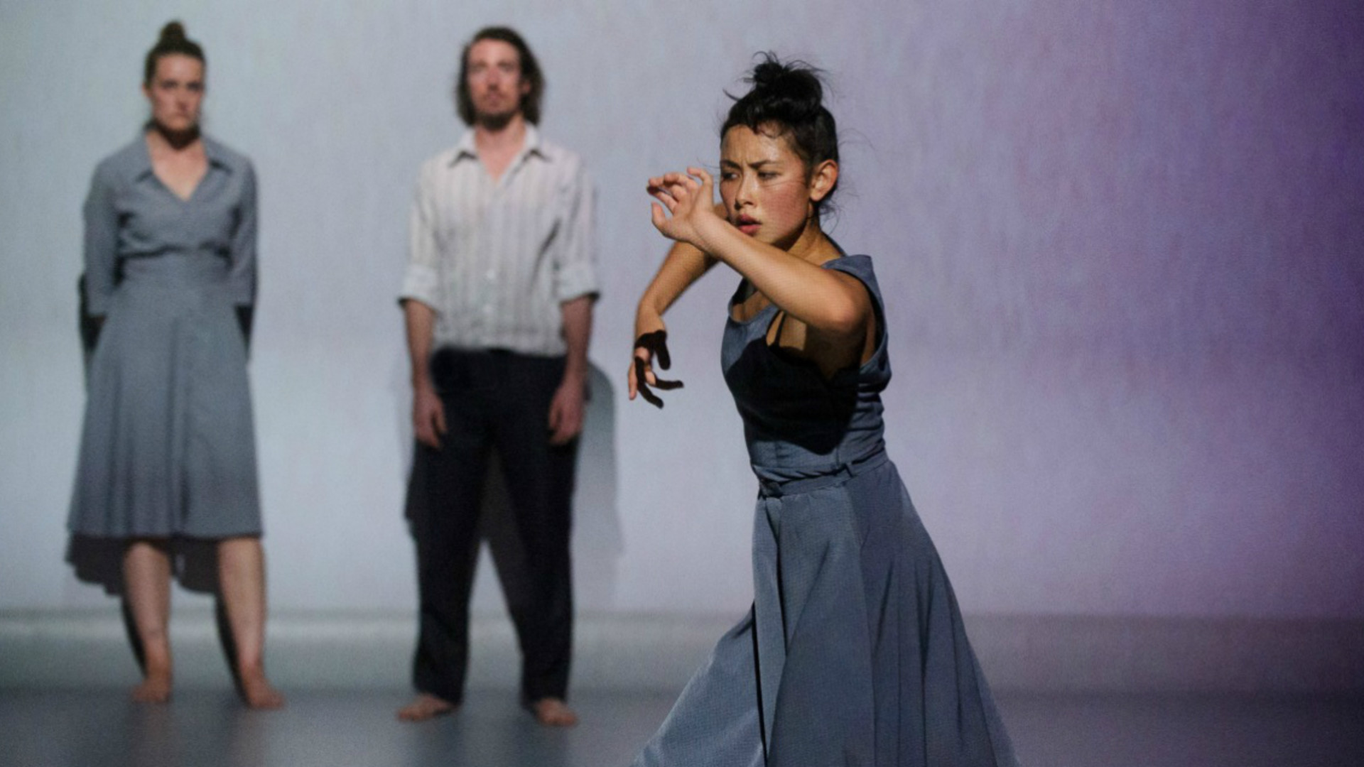 One dancer stands in the foreground with arms held up while two dancers stand in the background looking on.