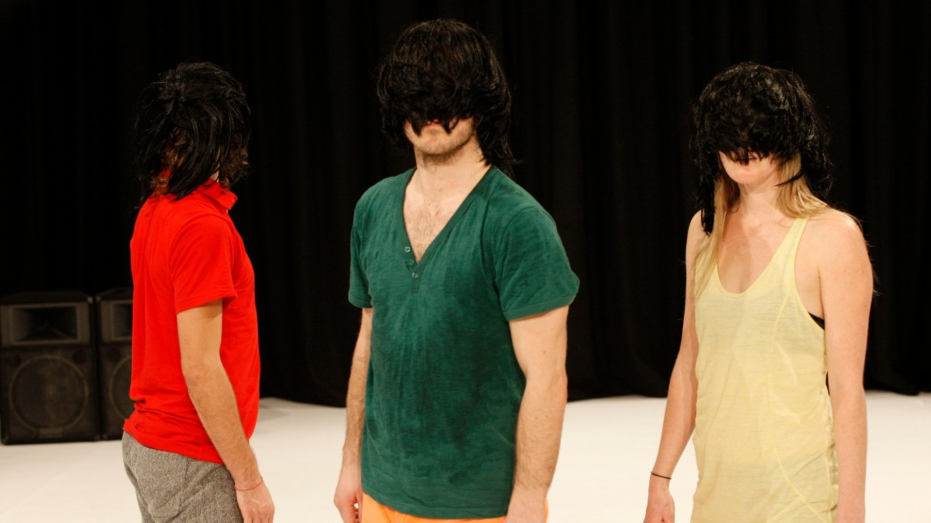 A close up of three dancers standing closely together with bright tops and wearing dark wigs which cover their faces