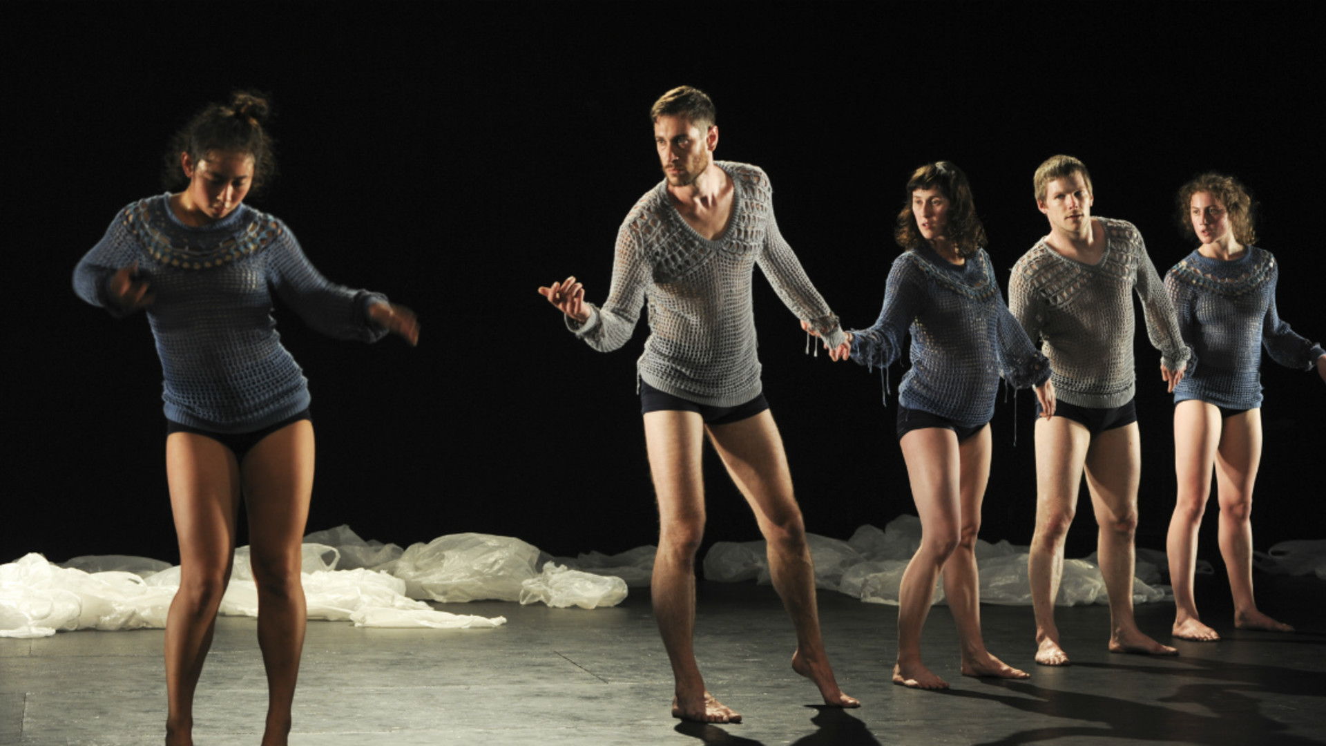 Dancers stand in a line, linking hands while another dancer sways her hips.